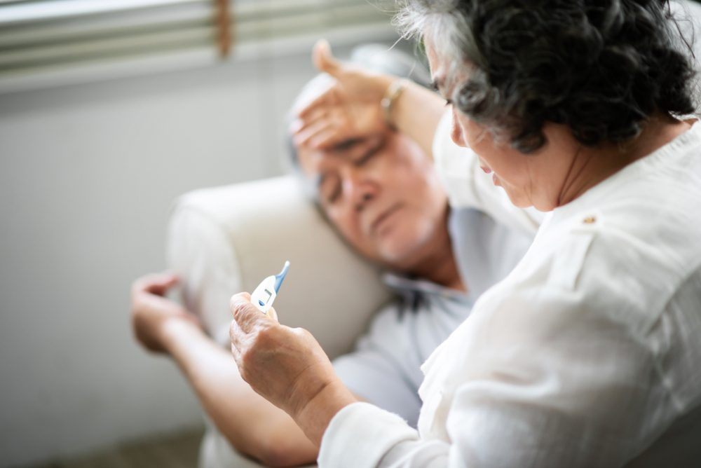 Sick Asian Senior man lying on sofa while his wife holding and looking to thermometer. illness, disease.