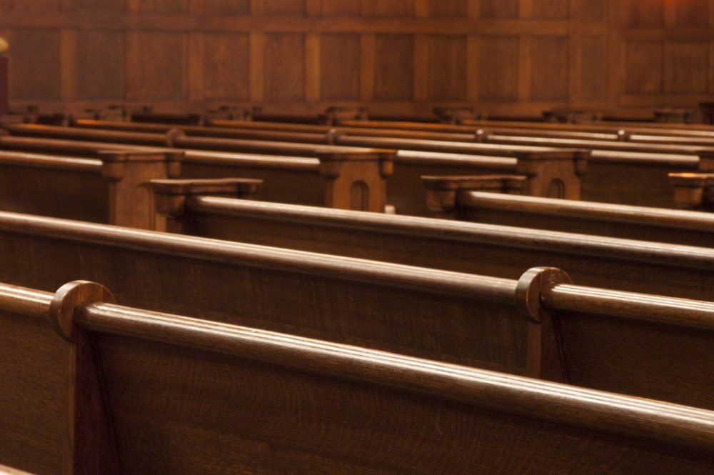Rows of wodden pews in a church