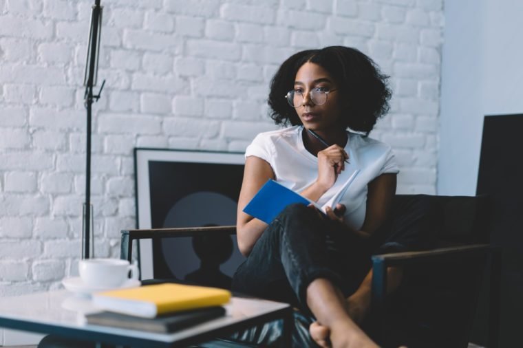 Thoughtful african american young woman in optical eyeglasses holding pen and thinking on creative ideas for writing her blog publication in notebook enjoying leisure time at home interior apartment