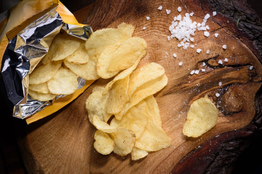 Snack of potato chips with sea salt over wooden background. Top view.