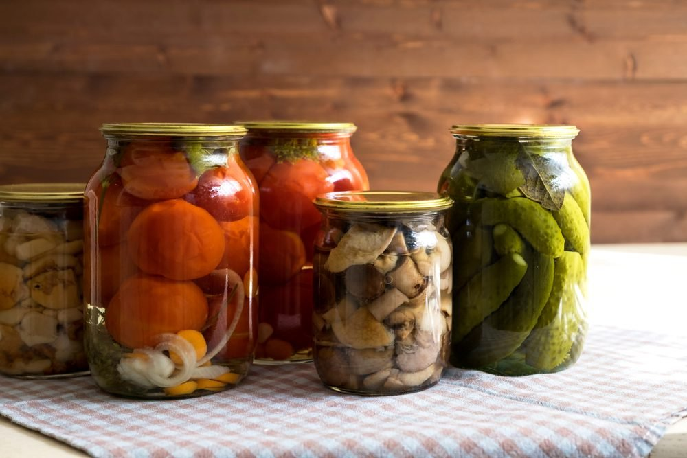 Marinated cucumbers, tomatoes and mushrooms in glass jars on the table.