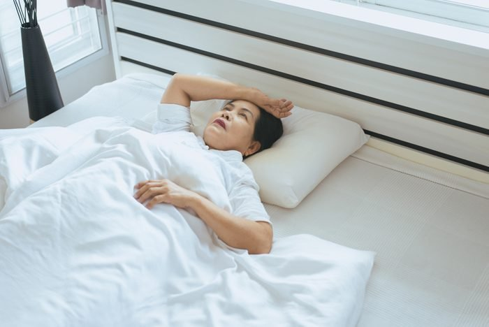 Insomnia in elderly asian women on her bedroom,Female lying suffering from headache at house