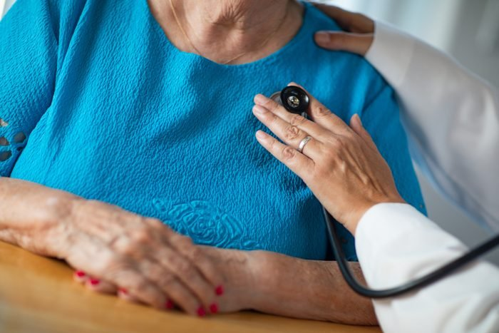 Female Doctor Checking The Heart With Stethoscope of Senior Adult Woman.
