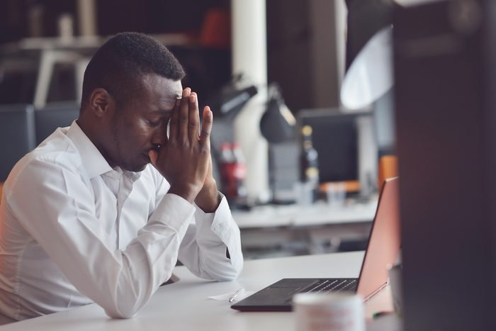 Tired African man sitting at a office after a hard workday, working on laptop, trying to concentrate