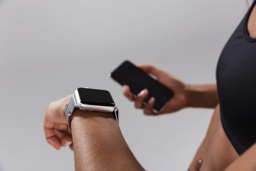 Close up of a young african sportswoman syncing mobile phone with smart watch isolated over gray background
