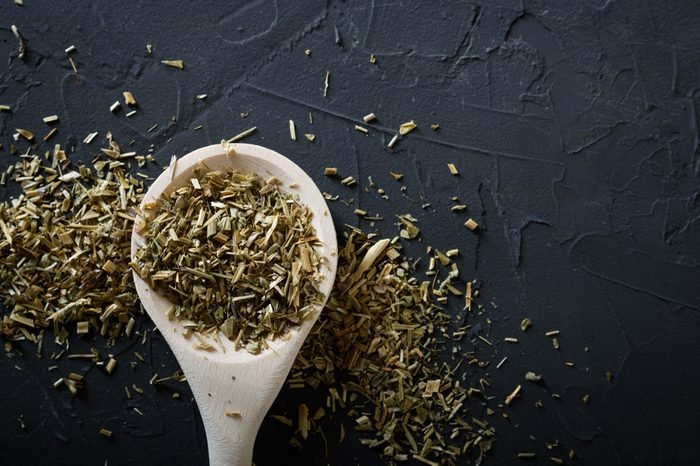 Wooden spoon with Italian seasoning-dried oregano with thyme,vegetables.Oregano in a wooden spoon on a rocky concretedark black background with a place for text Top view