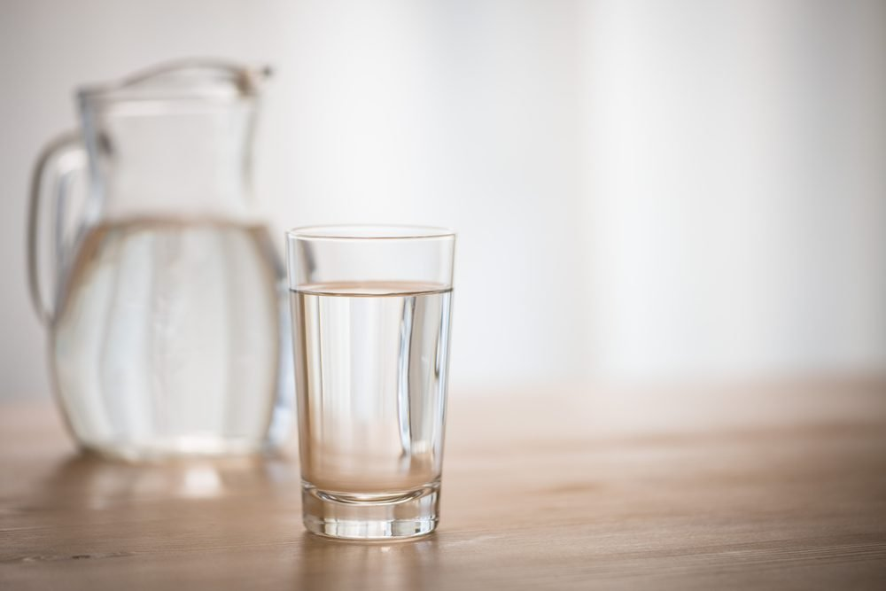 glass of water on a wooden table with a pitcher out of focus in the background