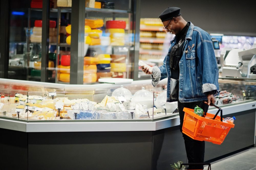 Stylish casual african american man at jeans jacket and black beret holding basket, standing near cheese fridge and shopping at supermarket.