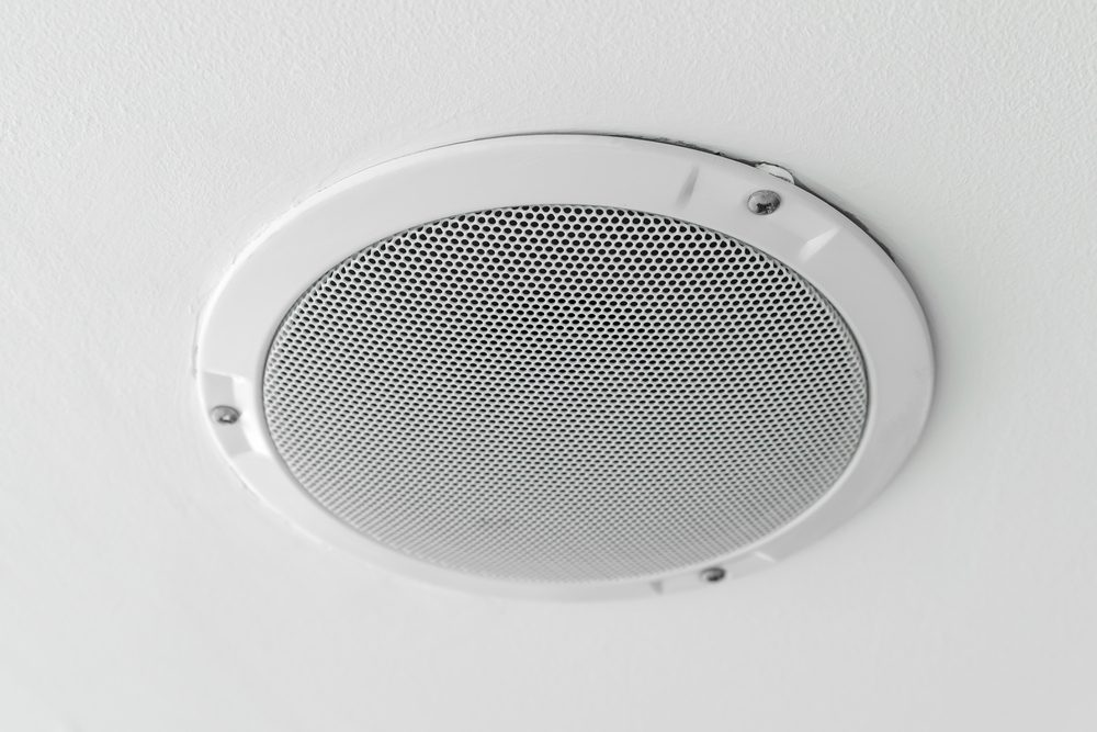 White round circle speaker and grille hanging on white ceiling