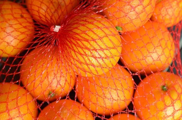 Fresh orange oranges in plastic netting In Market. Food background texture