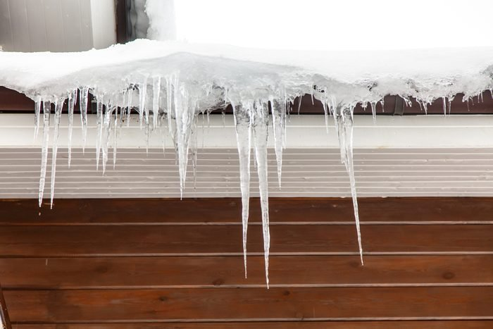 Icicles hang from the roof and dripping from them. Spring.