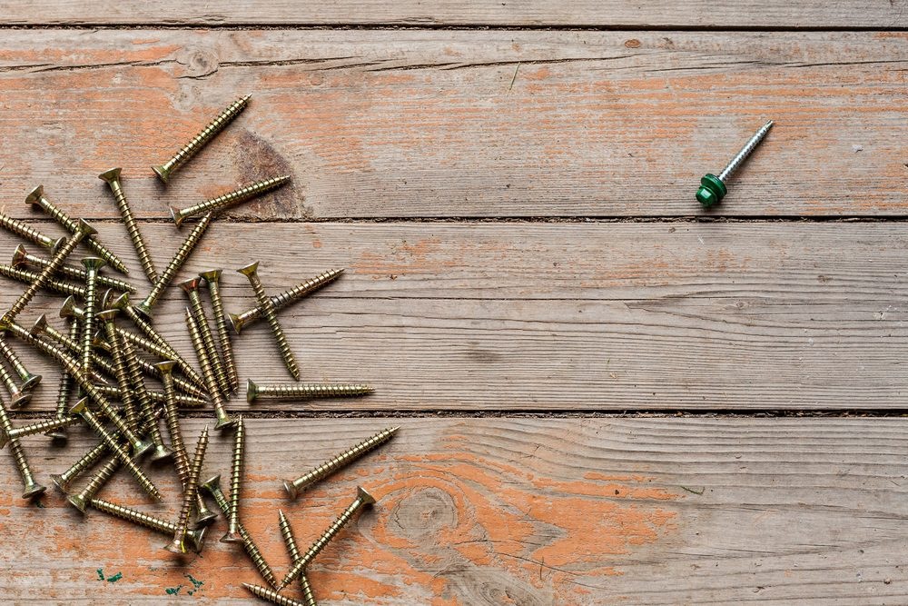 The arrangement with screws and bolts are distributed on a wooden table surface. Flat lay top view with Single steel roofing screw with a green hat