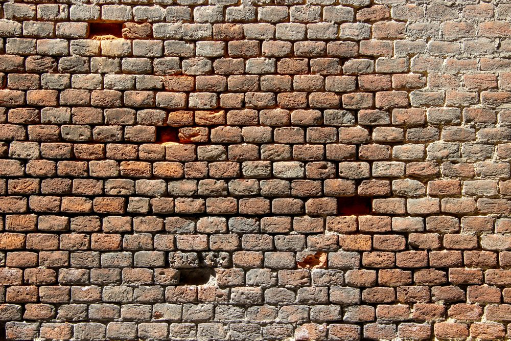 Old damaged brick wall with holes in place of some bricks