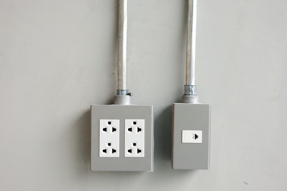 electrical outlet and light switches on cement wall