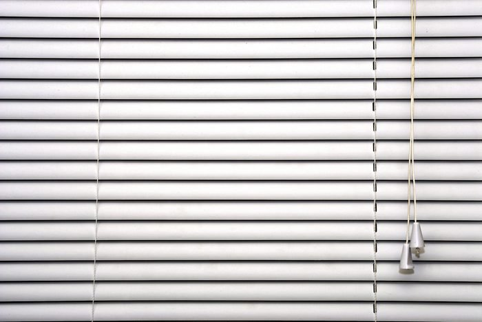 closed white blinds showing adjusting cords and slats
