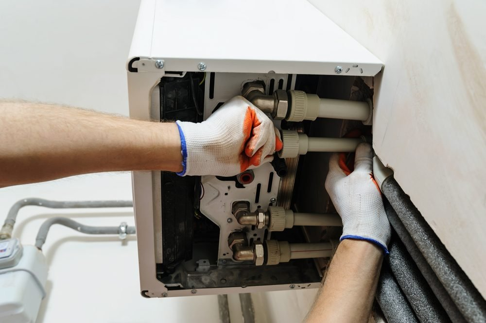 Installation of home heating. A worker attaches the pipe to the gas boiler.