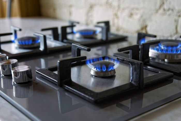 Cooktop with burning gas ring. Gas cooker with blue flames. Tinted photo.