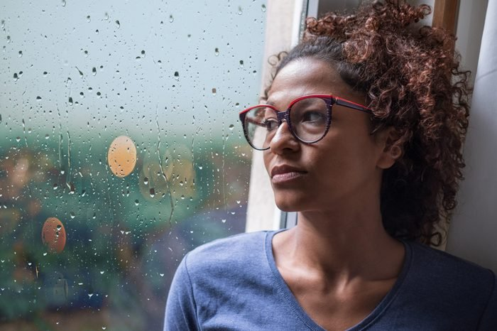 Sad woman looking out of the window on rainy weather