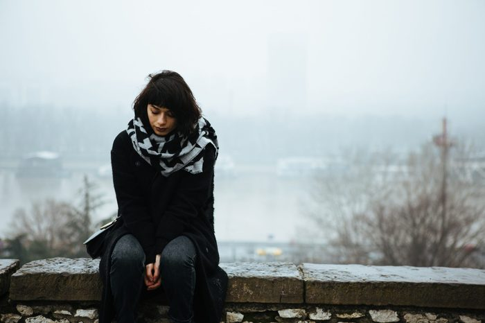 Girl sitting on a wall and having a tough time