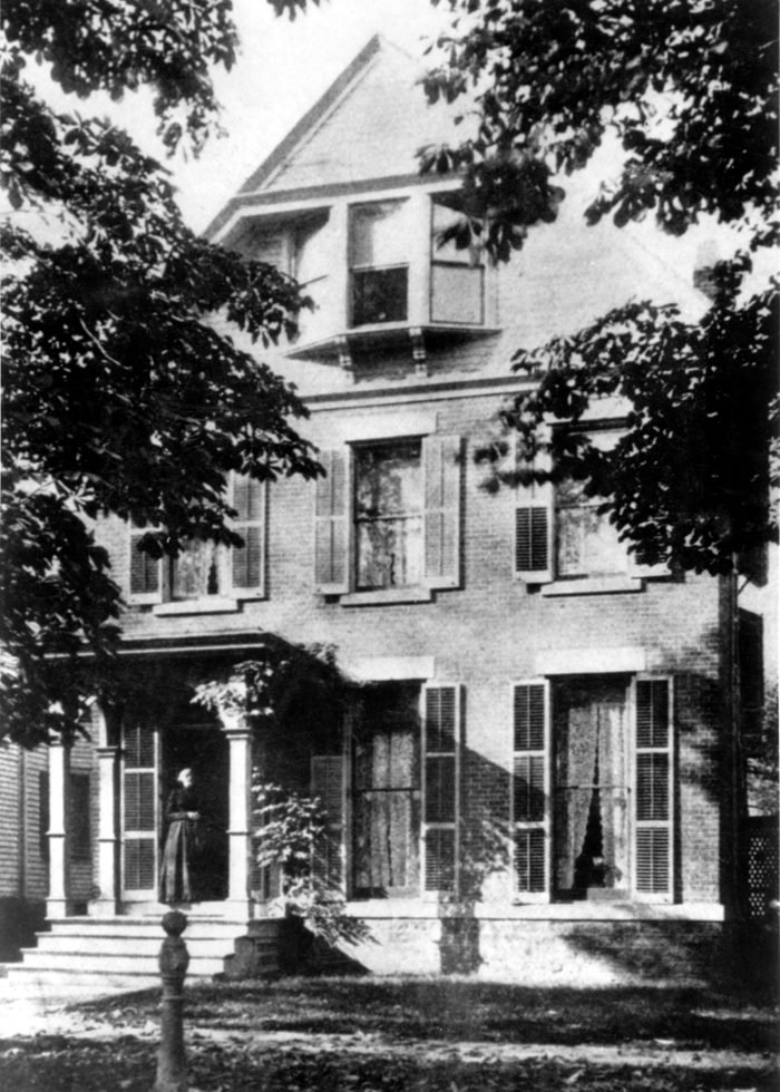 American abolitionist and suffragette Susan B Anthony (1820 - 1906) standing outside her home on 17 Madison Street, in Rochester, NY, late nineteenth century.