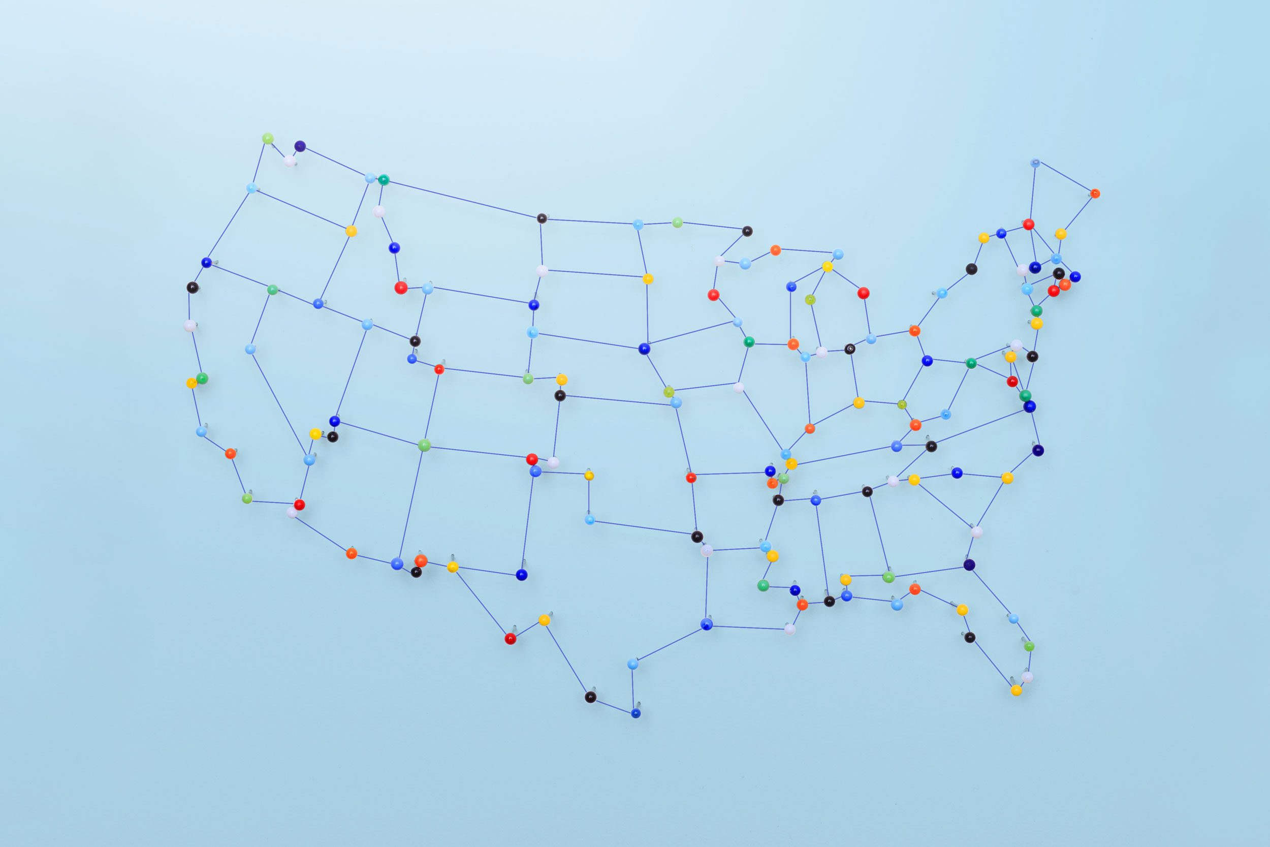 united states map made with pins and string on blue background