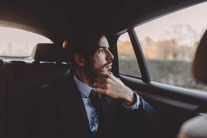 man looking pensively out the window of a taxi
