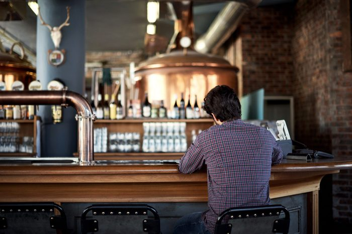 Rearview shot of a man sitting at a bar counter