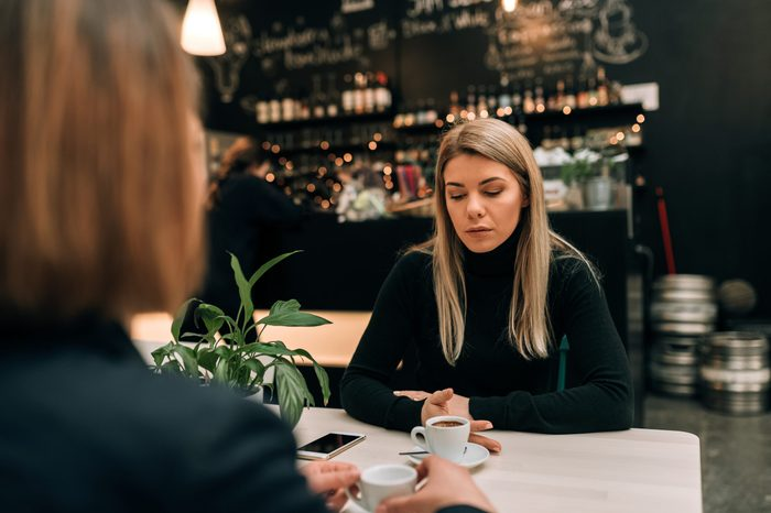 Two women in a cafe having a serious conversation over a cup of coffee