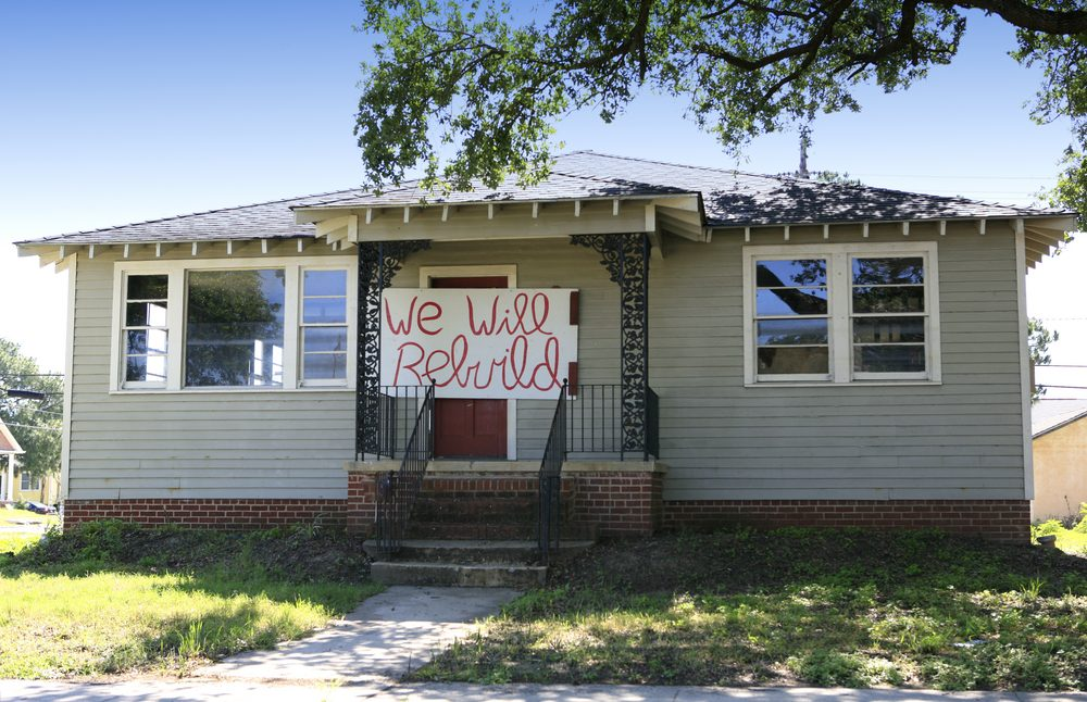 Katrina flood damaged house with rebuild sign on door