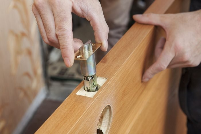 Installation locked interior door knobs, close-up woodworker hands install lock.