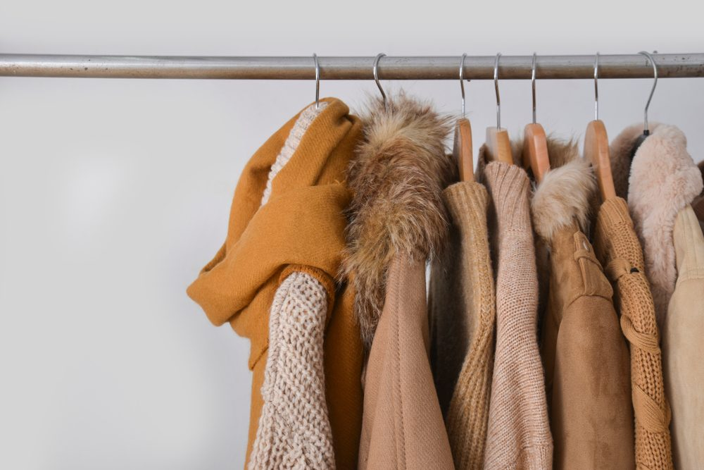 Set of fur jacket ,coat ,sweater, scarf , clothes on hanger –gray background