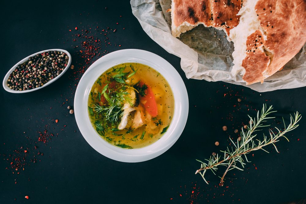 Ukha russian fish soup with trout, parsley, herbs and vegetables in it and a ground pepper nearby with rosemary, crushed pepper and a fresh bread on the craft paper on the dark background.