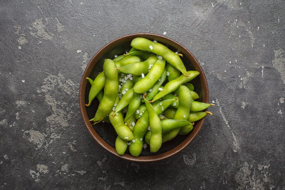 Fresh steamed edamame sprinkled with sea salt on a stone tabletop.
