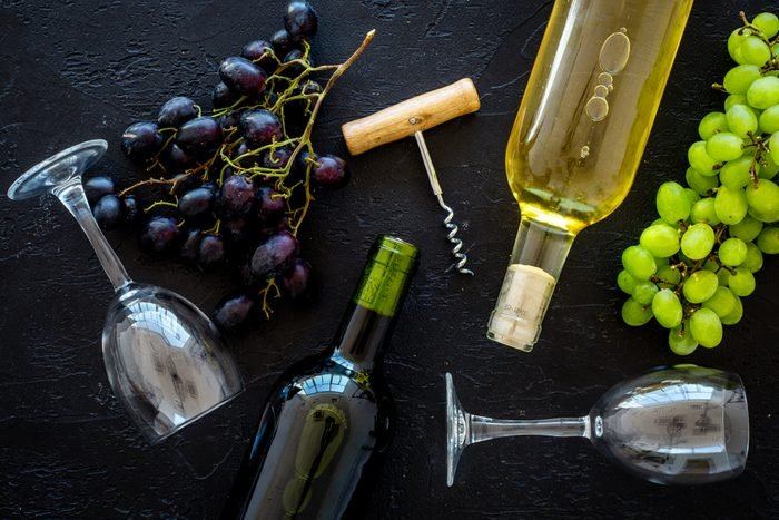 Composition with wine bottles. Red and white wine bottles, bunch of grapes, corkscrew, wine glasses on black background top view