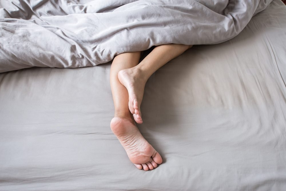 Barefoot and leg under blanket on the bed