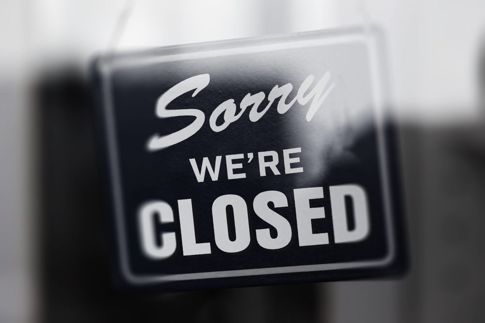 """ Sorry we're closed "" sign in monotone, with glass reflection. Shop glass door. Shallow depth of field."