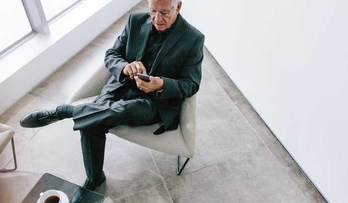 High angle view of senior businessman texting with mobile phone. Mature corporate professional reading emails on his smartphone during break.