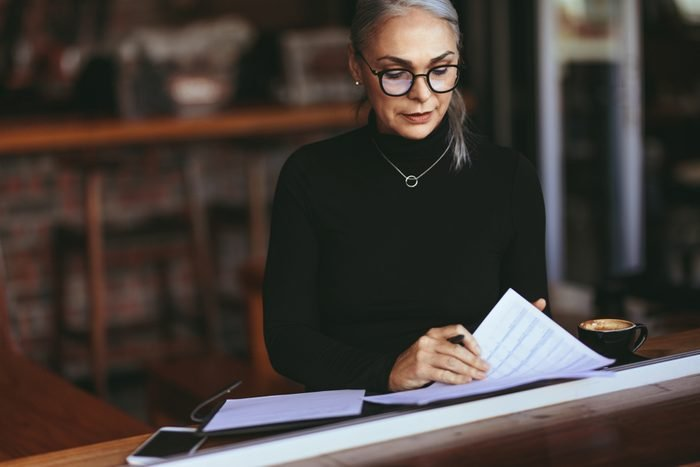 Mature woman sitting in a restaurant and doing some paperwork. Female sitting in cafe with a coffee reading some papers.