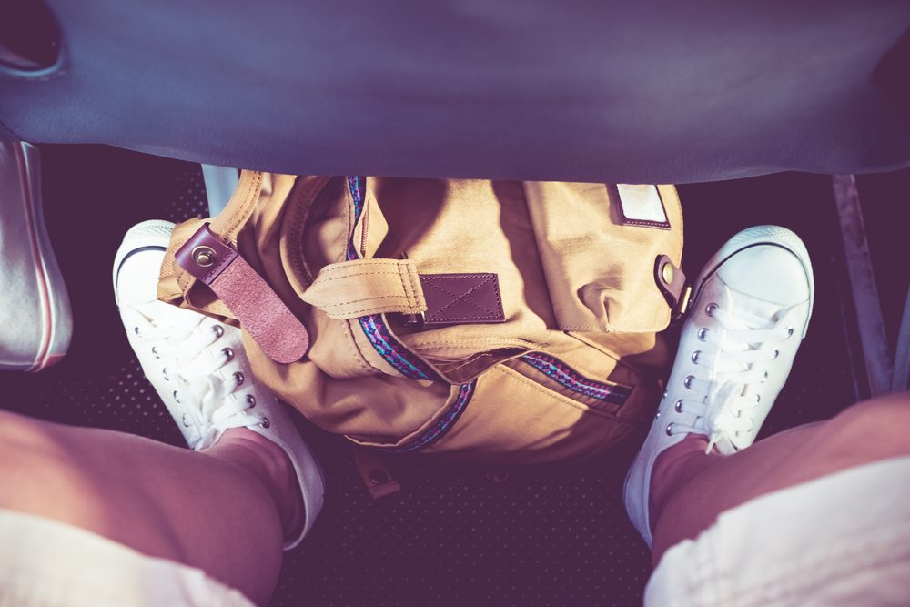Close up sneaker white shoe with backpack on floor under airplane seat,Vacation time concept