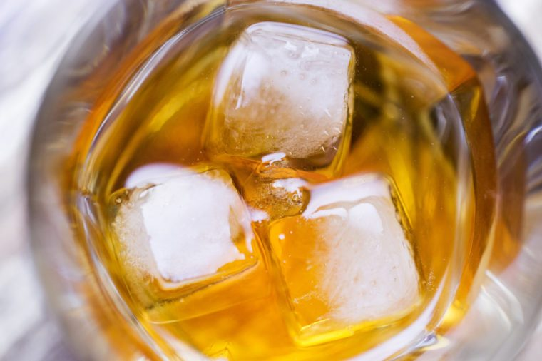 alcohol drinks and luxury concept - close up of ice in glass of whiskey