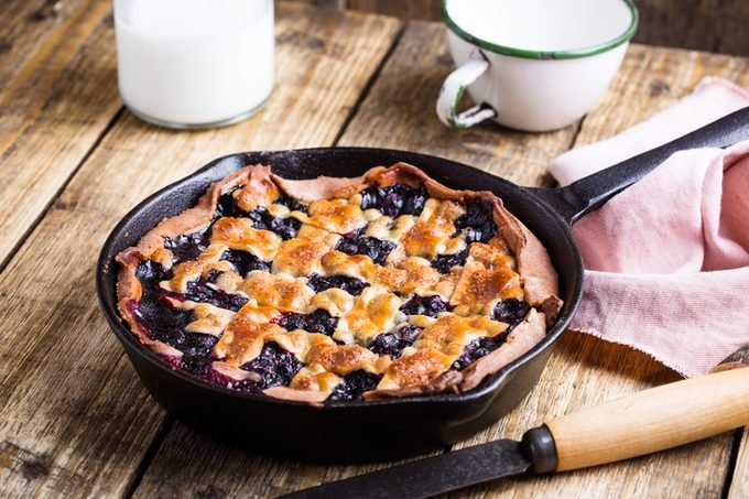 Rustic homemade blueberry pie in pan on wooden table, sweet treat