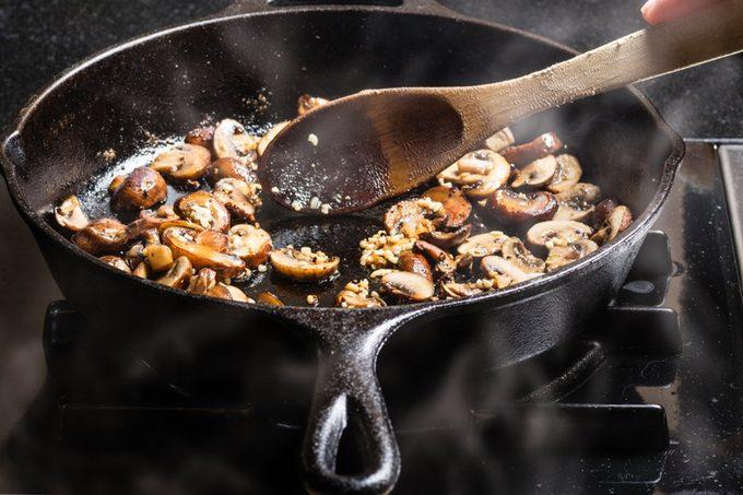 Sautéing sliced mushrooms in a cast iron skillet