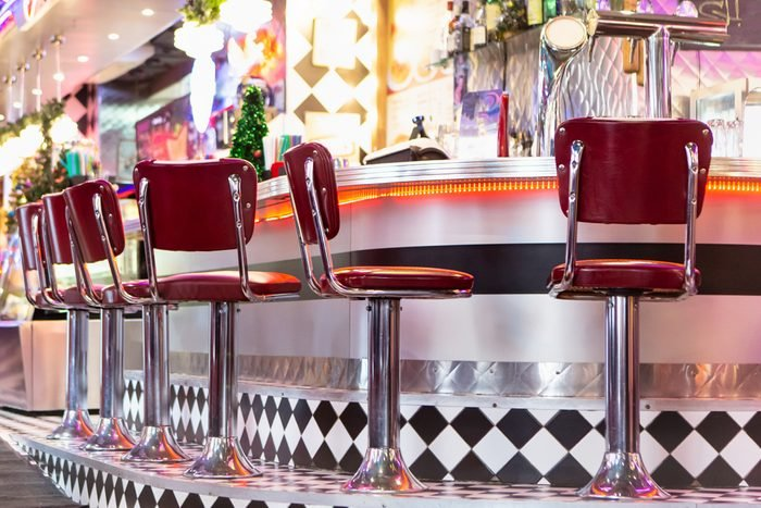Old Fashioned Red Bar Stools In American Burger Retro Diner Restaurant. Interior Of Bar Is In Traditional American Style. Long Bar Counter.