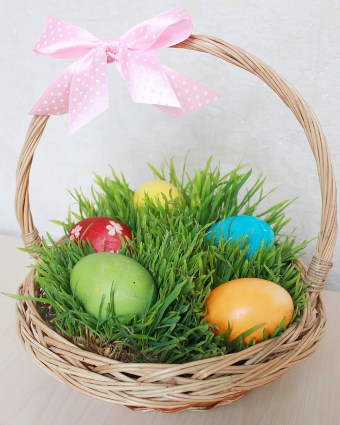 Basket with the Easter eggs on the grass