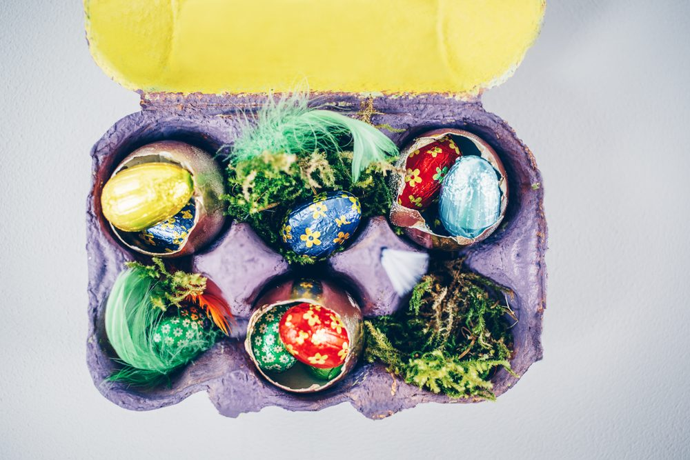 Simple Easter decoration with chocolate eggs , golden painted egg shells and natural materials in egg carton painted violet and yellow. View from above, copy space.