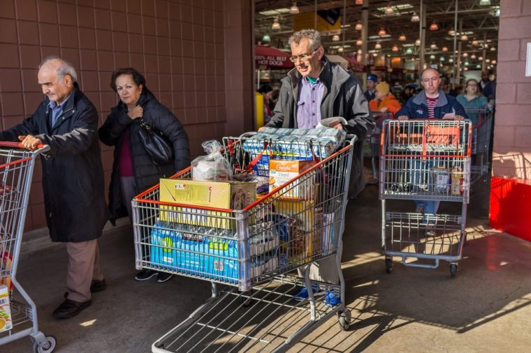 Fairfax, USA - December 3, 2016: People with shopping carts filled with groceries walking out of Costco store in Virginia