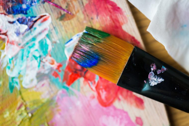 fine art, creativity, painting and artistic tools concept - close up of color palette and brush with paint