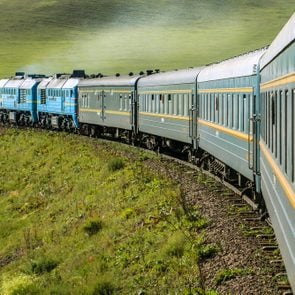 Transsiberian Railway with locomotive and steam crossing through Mongolia on a sunny summer day (near Ulaanbaatar, Mongolia, Asia)
