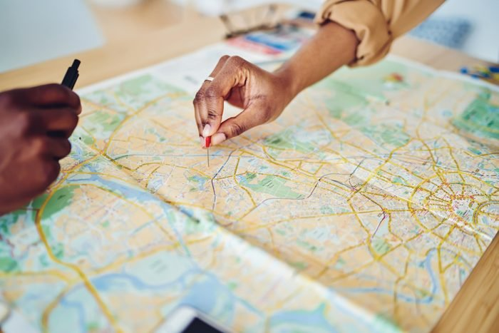 Cropped view of woman's hand pointing on mark on cartography planning touristic route on journey, closeup view of map of country checking direction and location for explore during travel vacation