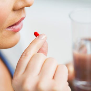 medicine, health care and people concept - close up of woman taking in pill